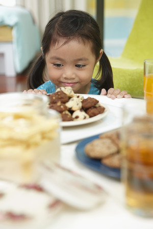 Girl smiling while looking at a plate of cookies