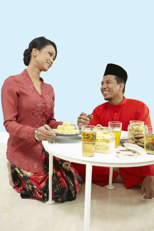 Woman serving man with a plate of cookies
