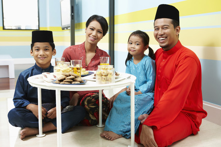 traditional celebrations: Family in traditional clothing sitting around coffee table LANG_EVOIMAGES