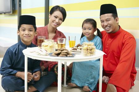 Familie in traditioneller Kleidung sitzen Couchtisch