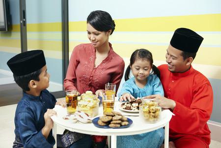 familia unida: Familia en la ropa tradicional que se sienta alrededor de la mesa de caf�