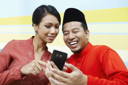Man and woman looking at mobile phone together LANG_EVOIMAGES
