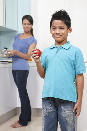 malay boy: Boy holding red apple, woman in the background