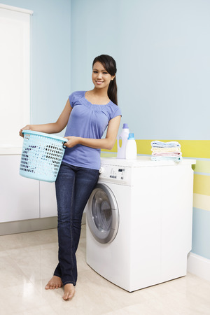 laundry basket: Woman with laundry basket standing next to washing machine