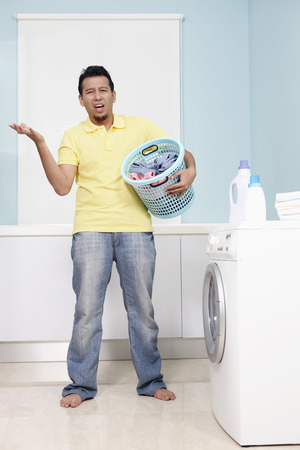man laundry: Man with laundry basket looking confused