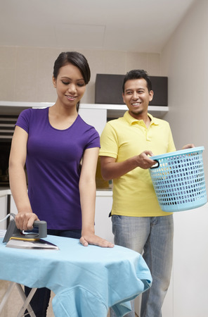 laundry basket: Woman ironing clothes, man carrying laundry basket in the background