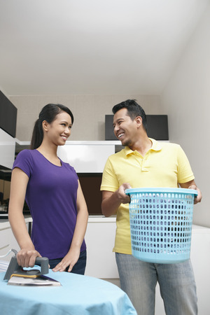 house chores: Man and woman looking at each other while doing house chores