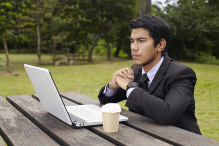 Young Asian businessman in a park with his laptop Imagens