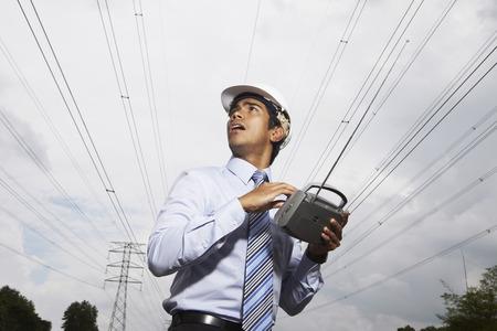 tuning: Young businessman tuning portable radio