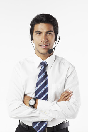 handsfree device: Young businessman wearing headset with arms crossed