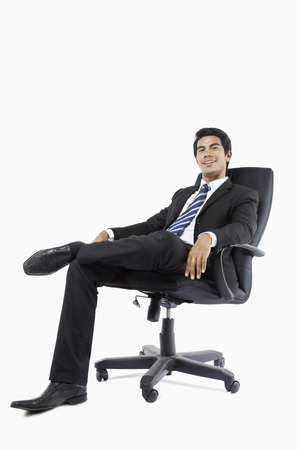 legs crossed at knee: Confident young businessman seated in an office chair LANG_EVOIMAGES