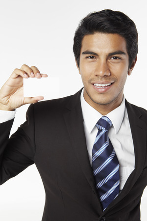 holding business card: Young businessman holding business card