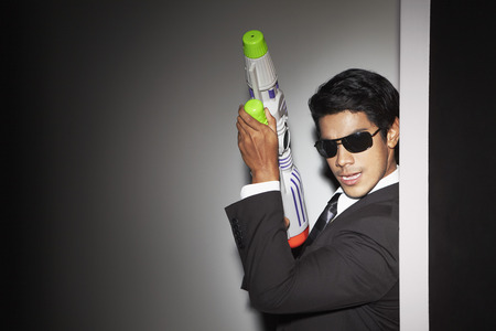 out of context: Young businessman fooling around with squirt gun