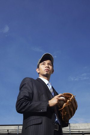 baseball glove: Young businessman with a cap equipped with baseball glove and ball