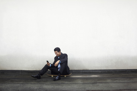 text messaging: Young businessman sitting on skateboard, text messaging on phone