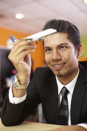 model airplane: Young businessman playing with model airplane