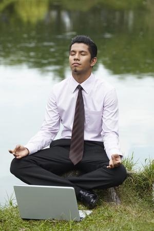 crosslegged: Young businessman sitting cross-legged, meditating