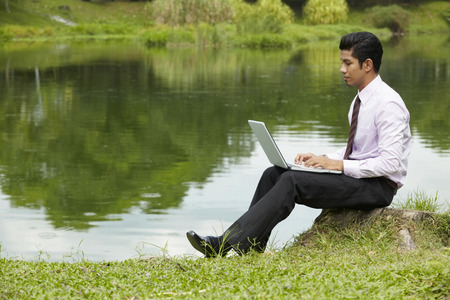 Young businessman using laptop outdoors Stock Photo