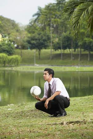 en cuclillas: Hombre de negocios joven en cuclillas y la celebración de una pelota de fútbol