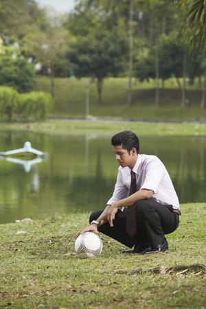 cuclillas: Hombre de negocios joven en cuclillas, sosteniendo una pelota de f�tbol