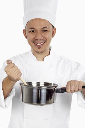 saucepan: Asian chef cooking with saucepan