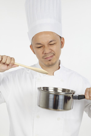stress testing: Asian chef cooking with saucepan, looking disappointed LANG_EVOIMAGES