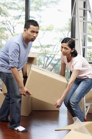 Man and woman lifting cardboard box together Stock Photo