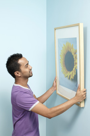 putting up: Man putting up new painting on wall LANG_EVOIMAGES