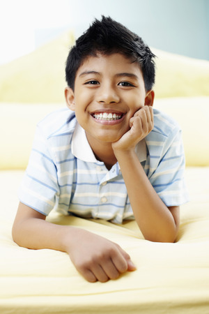 lying forward: Boy lying forward in bed smiling LANG_EVOIMAGES