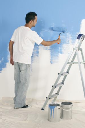 hombre pintando: Hombre de pintura con rodillo de pared