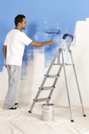 man painting: Man painting wall with roller