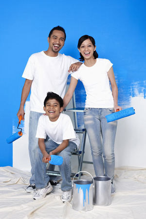 Family with paint rollers getting ready to paint the wall