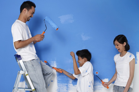 family with one child: Family playing while painting wall