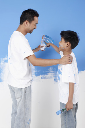 letting: Man letting boy choose color from color swatches