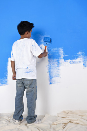 malay boy: Boy painting wall with paint roller