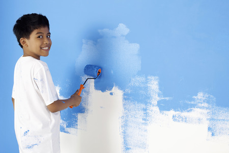paint roller: Boy painting wall with paint roller