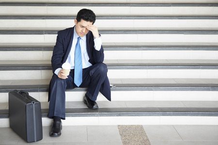 worried businessman: Worried businessman sitting on stairway, contemplating