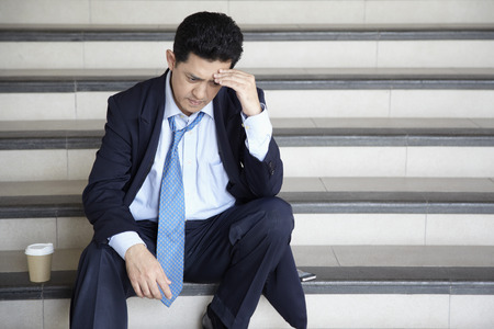 scowl: Worried businessman sitting on stairway, contemplating
