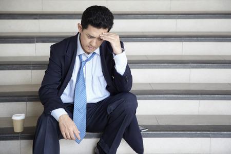 worried businessman: Worried businessman sitting on stairway, contemplating