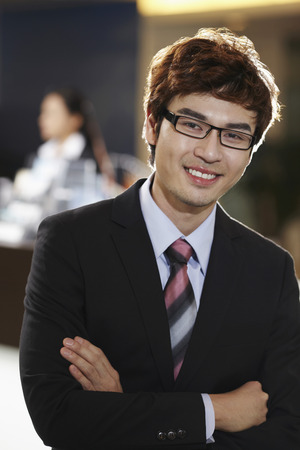 business: Businessman smiling with arms crossed