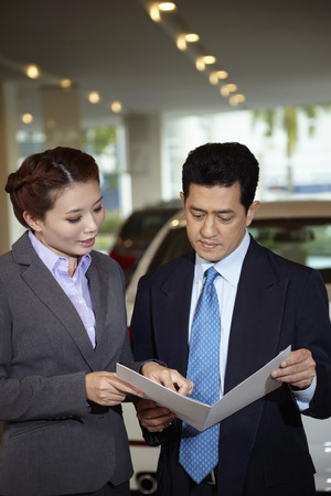 sales representative: Sales representative explaining to customer specifications of the car form a brochure