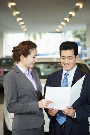 specifications: Sales representative explaining to customer specifications of the car form a brochure