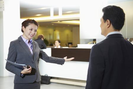 car dealership: Sales representative of car dealership ushering customer to the counter LANG_EVOIMAGES