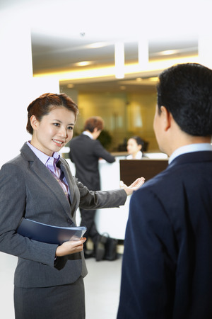 Sales representative of car dealership ushering customer to the counter Stock Photo