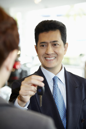 handing over: Sales representative handing over keys to customer in car showroom