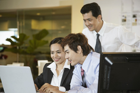 three people only: Businesswoman using laptop with her colleagues watching on