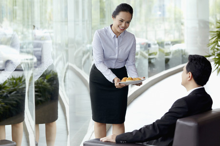 sales representative: Sales representative serving customer with some pastries