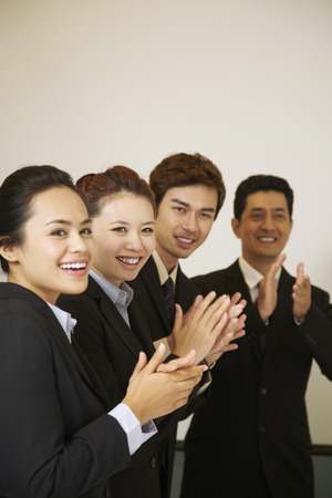 Business people standing in a row, clapping their hands
