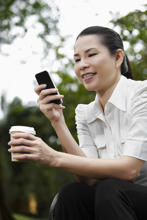 text messaging: Mid adult businesswoman text messaging on smart phone LANG_EVOIMAGES