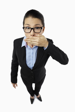 covering mouth: Mid adult businesswoman covering mouth